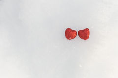 Little red shiny hearts. In the snow Stock Photo