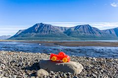Travel of little red car. Little red toy car on coast of Lama lake Putorana plateau, Russia beyond of Arctic circle Royalty Free Stock Photo