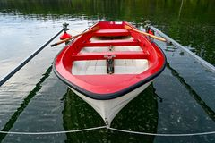 Little red and white skiff in Swedish lake stock photography