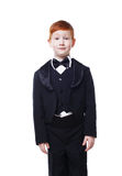 Little redhead boy in tailcoat tuxedo, portrait isolated on white Stock Image