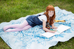 Little redhead girl drawing. With pencils on the plaid on the grass royalty free stock photography