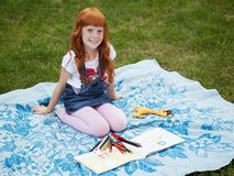 Little redhead girl drawing. Little redhead girl sitting on the plaid with pencils and album for drawing stock image