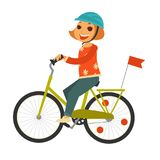 Little redhead girl in helmet rides bicycle with flag Royalty Free Stock Photo