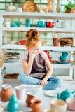 Redhead girl sitting at clay workshop studio with many cup. Little redhead girl sitting at clay workshop studio with many cup Royalty Free Stock Image