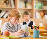 Little redhead schoolboy behind desk Stock Image