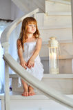 Little redheaded girl. On white stairs Stock Photo