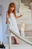 Little redheaded girl. On white stairs Stock Photos
