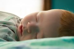 A Sleeping infant. A little redheaded infant sleeping Royalty Free Stock Image