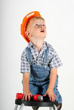 Little Repair man. Cute toddler boy in an orange hard hat and a power drill climbing a chair and looking up at the ceiling light he wants to repair royalty free stock images