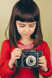 Little retro photographer with an old camera. Little retro photographer girl with red nails holding an old medium format camera. Some film grain and vintage Stock Photo