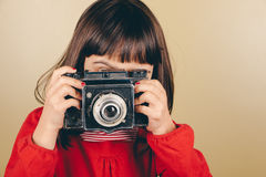 Little retro photographer with an old camera Stock Image