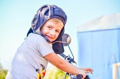 Little rider. Little smiling boy with retro  helmet sitting on old scooter in a garden Royalty Free Stock Photo