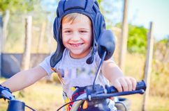 Little rider. Little smiling boy with retro  helmet sitting on old scooter in a garden Stock Images