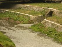 Little river with big sewer opening. With ctone walls and plants royalty free stock photos
