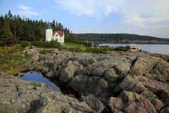 Little River Lighthouse with Rocks and Water. Little River Lighthouse is featured in this iconic coastal Maine image. The lighthouse with its foghorn stands out Stock Images