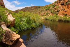 Little river winds between red mountains Royalty Free Stock Image