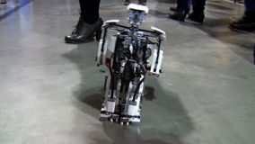 Little robot walking. A little robot made from plastic details walking on the concrete floor between people stock video