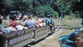 LITTLE ROCK, ARKANSAS 1957: Folks riding a mini narrow track train around the park. Original vintage 8mm film home movie professionally cleaned and captured in stock video footage