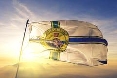 Little Rock-Stadthauptstadt von Arkansas des Flaggentextilstoffgewebes Vereinigter Staaten, das auf den Spitzensonnenaufgangnebel stockbilder