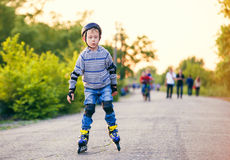 Little roller skater in the evening park Stock Photo