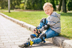Little roller skater put on his skates Royalty Free Stock Photos