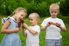 Little rothers and sister eating chocolate Stock Images