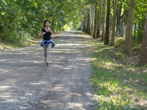 Little run. Shapely woman is running on the abandoned road Stock Images