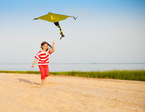 Little running girl with flying kite on beach at sunset Royalty Free Stock Photos