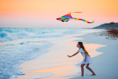 Little running girl with flying kite on tropical beach at sunset. Kids play on ocean shore. Child with beach toys. Stock Images