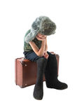 The little Russian boy in a fur hat and boots sitting on old suitcase and thinking Royalty Free Stock Photo