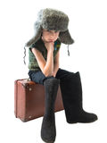 The little Russian boy in a fur hat and boots sitting on old suitcase and thinking Stock Images