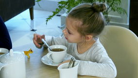 Little russian girl holding spoon and stiring sugar in tea at restaurant. stock footage
