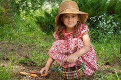 Little Russian Girl And Mushroom. Adorable Little Six Year Old Girl Russian In Wicker Hat With Basket In her hand Gladly Picking Mushrooms Suillus, Half-sitting Royalty Free Stock Photo