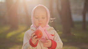 A little Russian girl in a pink headscarf eat red apple at sunset stock footage