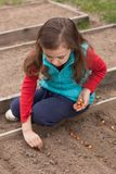 Russian Girl Planting Seeds Of Onion On Ground. Royalty Free Stock Images