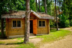 Log cabin in woods. A little rustic log cabin in the woods with open door in sunny day royalty free stock photo
