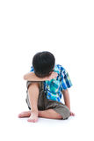 Little sad boy bare feet sitting on floor. Isolated on white bac. Kground. Negative human emotions. Conceptual about children who lack warmth and affection Stock Photos