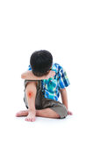 Little sad boy bare feet sitting on floor. Isolated on white bac. Little sad boy bare feet sitting on floor, bruise on leg after accident, child painful Royalty Free Stock Images