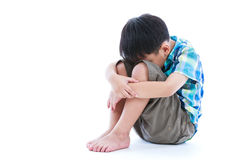 Little sad boy barefeet sitting on floor. Isolated on white back. Ground. Negative human emotions. Conceptual about children who lack warmth and affection Royalty Free Stock Images