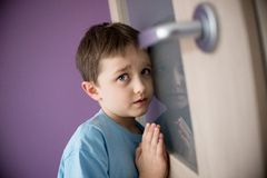 Little sad boy overhears fight of his parents - B&W Stock Image