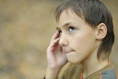 Little sad boy. Portrait of a sad boy in autumn park Royalty Free Stock Photos