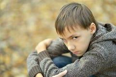 Little sad boy. Portrait of a happy little sad boy in autumn park Royalty Free Stock Image