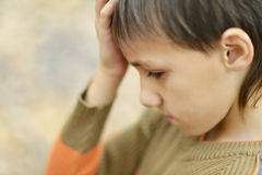 Little sad boy. Portrait of a happy little sad boy in autumn park Royalty Free Stock Photos