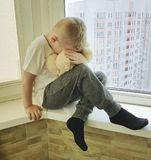 Little sad boy sits expression problem cries unhappy on a window with a teddy bear lonely Royalty Free Stock Images