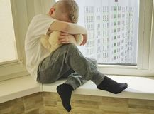 Little sad boy sits expression problem  unhappy on a window with a teddy bear lonely Royalty Free Stock Photo