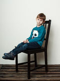 Little sad boy is sitting on the chair along Royalty Free Stock Photography