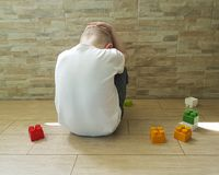 Little sad boy sitting on the floor with a block  depression   frustrated. Little sad boy sitting on the floor with a block unhappy   frustrated depression Royalty Free Stock Image