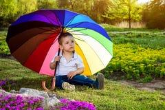 Little sad boy sitting under colorful umbrella in the garden. Little sad boy sitting under colorful umbrella in spring garden royalty free stock image