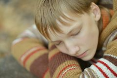 Little sad boy. In a warm sweater in the autumn park Stock Photo