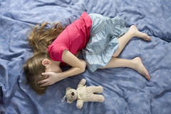 Little sad crying girl with teddy-bear. Little sad crying girl lying on the bed royalty free stock photography